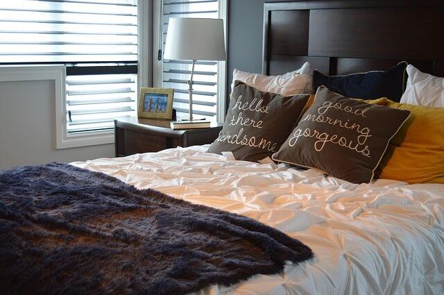 Łóżko z poduszkami, pościelą i kocem