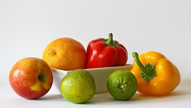 Kolorowe owoce i warzywa z białą salaterką, na białym tle