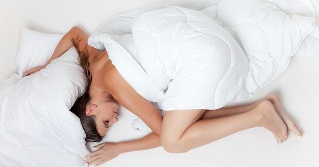 Zasypiająca kobieta w łóżku, w białej pościeli