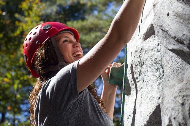 Usmiechnięta kobieta wspian się na skałce