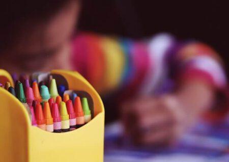dziecko rysuje kredkami