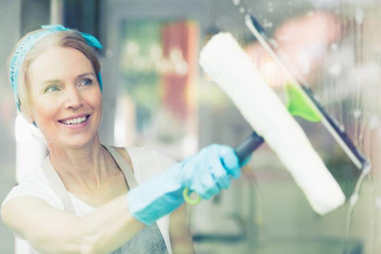 Kobieta czyści okno