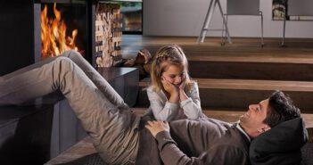 Ojciec i córka siedzący przed kominkiem